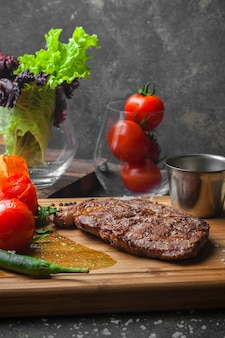 Side view steak with tomato and paper in steak board