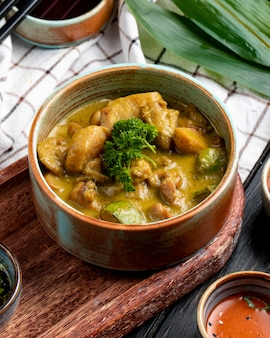 Side view of stewed chicken with vegetables in a clay bowl on plaid tablecloth