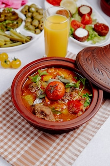 Side view of stewed meat with potatoes and tomatoes in a clay pot