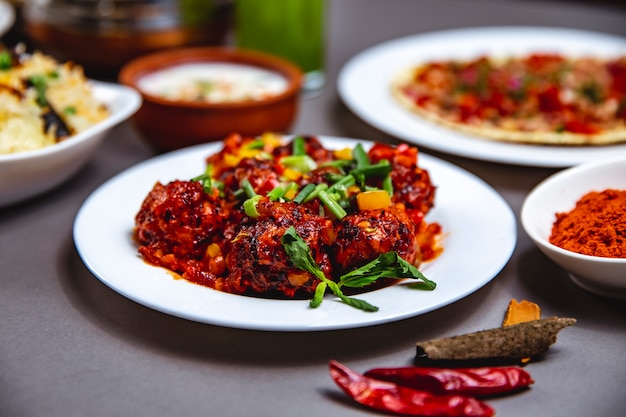 Side view stewed meatballs with tomato sauce bell pepper spring onion and mint on a plate