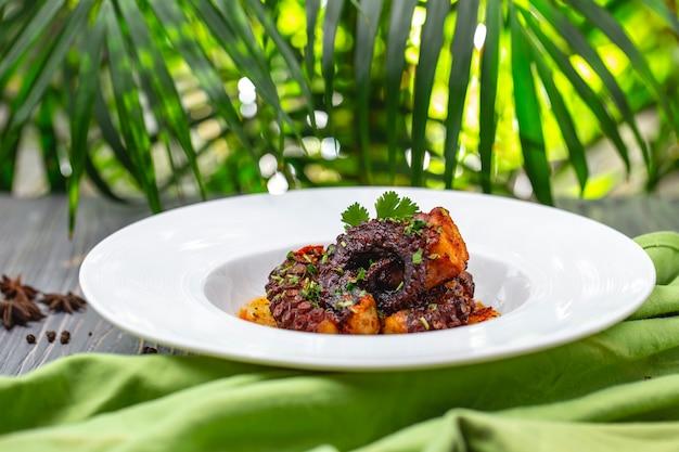 Вид сбоку тушеный осьминог с картофелем и зеленью на тарелке