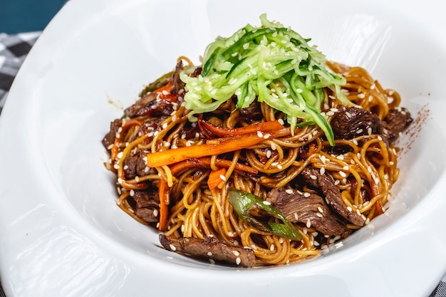 Side view stir fried noodles with grilled red meat carrot cucumber and sesame seeds on a plate