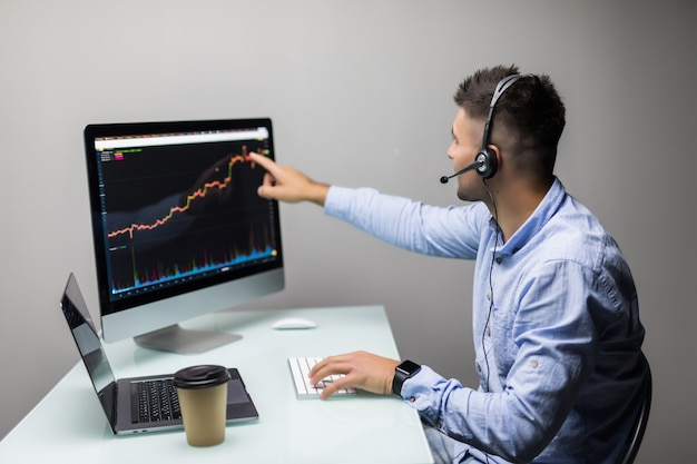 Side view of stock market broker talk headphones looking at graphs on multiple screens in office