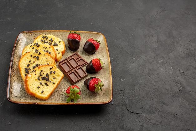 テーブルの左側の灰色のプレートにイチゴとケーキケーキとチョコレートで覆われたイチゴの側面図