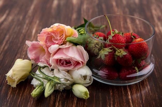 Side view of strawberries in bowl and flowers on wooden background