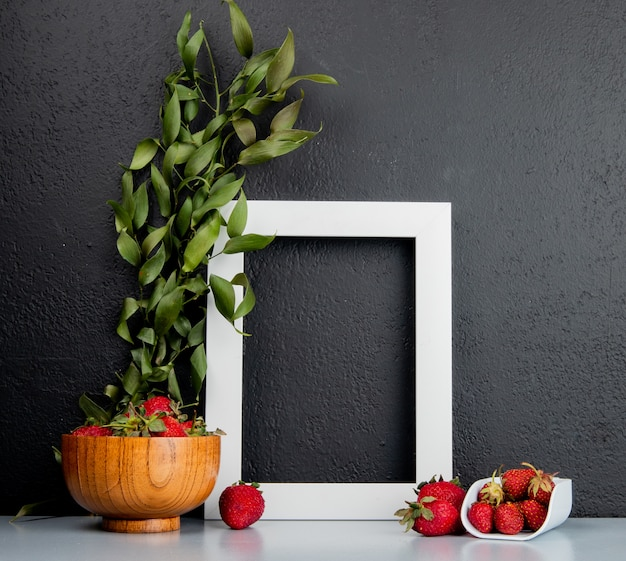 Side view of strawberries in bowl with frame on white surface and black background decorated with leaves with copy space