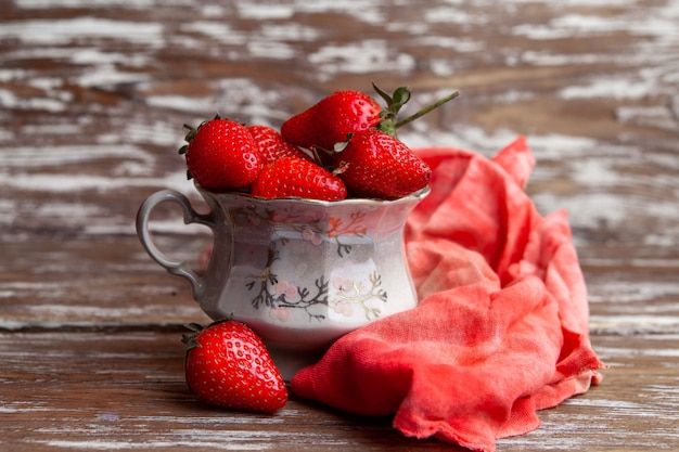 Side view strawberries in a coffee cup with red cloth on wooden background. horizontal