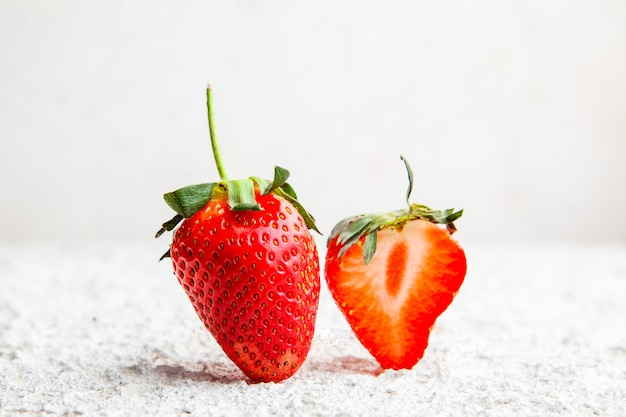 Side view strawberries on white textured background. horizontal