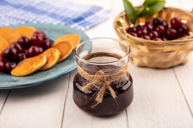 Vista laterale della marmellata di fragole in vaso e piatto di frittelle e ciliegie con cesto di ciliegie su fondo di legno