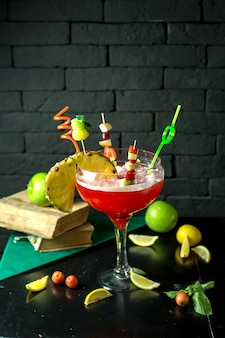 Side view of strawberry lime margarita cocktail with a piece of pineapple in glass on dark