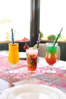 Вид сбоку клубничный мохито с апельсиновым соком и красочным коктейлем на столе