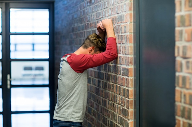 Side view of stressed man leaning on wall