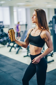 Side view of a strong athletic girl with yellow flask of water on the gym. beautiful sportswoman in black top and tights holding shaker after training in the fitness center.