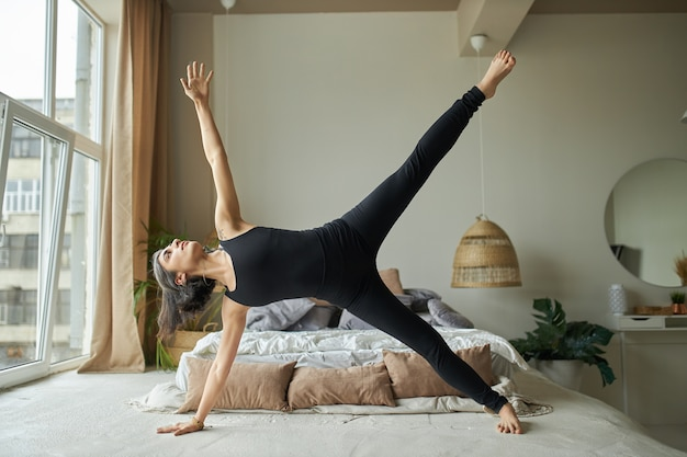 Side view of strong athletic young woman practicing yoga in cozy bedroom, standing in siide plank exercise