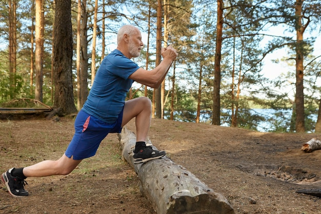 Vista laterale di uomo anziano forte in forma con la barba che lavora nella foresta, affondi doig, mantenendo i piedi sul registro maschio anziano concentrato facendo esercizi fisici per i muscoli delle gambe in una giornata di sole estivo