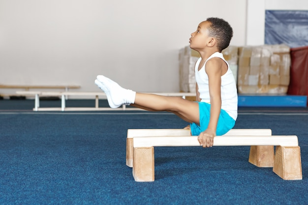 Side view of strong flexible dark skinned male child in sportswear doing exercises on wooden