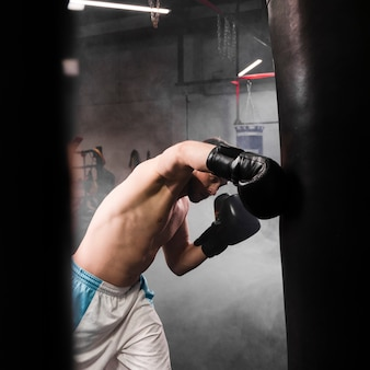 Side view strong male boxer training for a competition