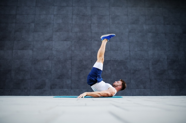 Side view of strong muscular caucasian man in shorts and t-shirt doing candlestick exercise on mat outdoors. in background is gray wall.