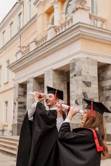 Боковой вид студентов, использующих диплом в качестве бинокля