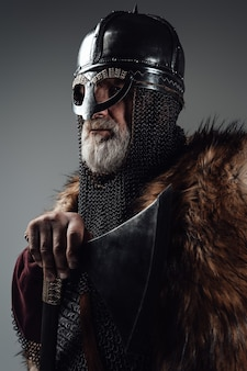 Side view studio shot of isolated in gray background old man viking wielding axe.