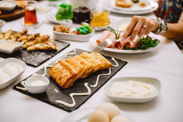 Vista laterale di pancake ripieni con salsa di carne e crema su un bordo nero