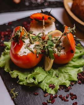 Вид сбоку фаршированные помидоры с соусом на листе салата с нарезанным лимоном и сушеной барбарисом