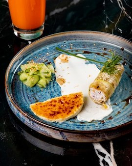 Vista laterale ripieni di zucchine con una fetta di formaggio e cetriolo su un piatto blu