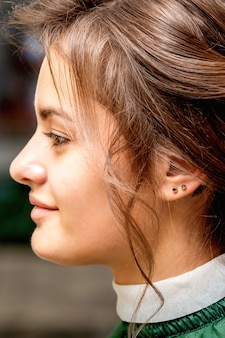 Side view of styling hair of the beautiful young caucasian brunette woman in a beauty salon