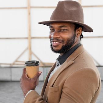 Вид сбоку стильный афро-американский мужчина держит чашку кофе