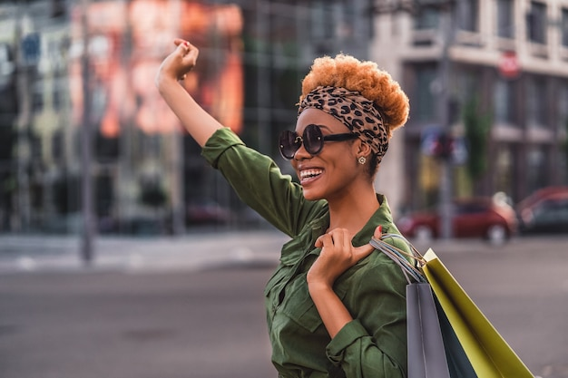 Side view of stylish afro american lady in sunglasses waving hand while walking in the city and holding shopping bags