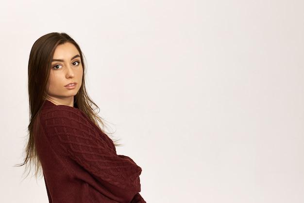 Vista laterale di elegante fiduciosa giovane donna dai capelli scuri in caldo maglione accogliente incrocio le braccia sul petto e sorride alla macchina fotografica in posa su sfondo bianco con spazio di copia