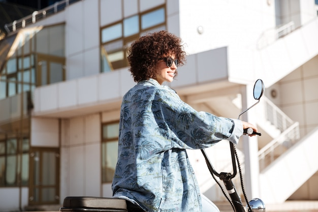 Side view of stylish curly woman in sunglasses posing on modern motorbike outdoors