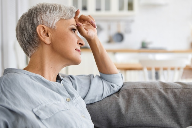 Side view of stylish elderly mature woman with neat make up and short hair relaxing on sofa at home, having thoughtful dreamy facial expression. retired female sitting on couch in living room