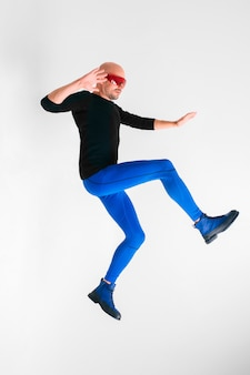 Side view of stylish man in futuristic red glasses and blue tights lying in air