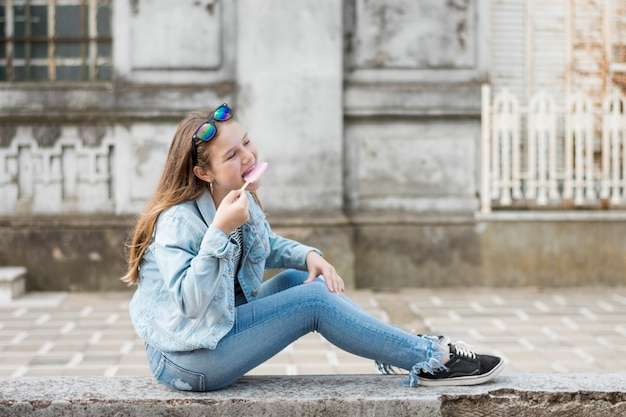 Side view of stylish teenage girl siting on wall eating ice-cream