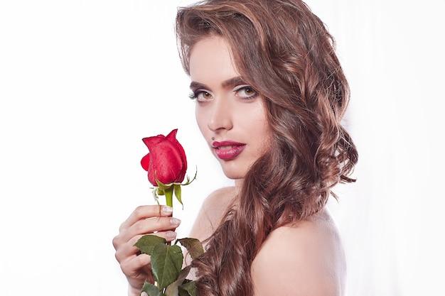 側面図。赤いバラのスタイリッシュな若い女性。白い背景で隔離
