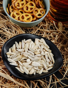 Side view of sunflower seeds in a black bowl with mini pretzels and a mug of beer on straw