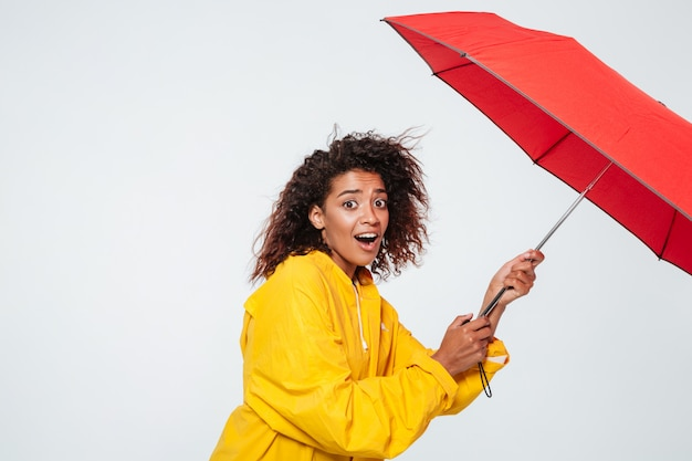 Side view of surpised african woman in raincoat holding umbrella
