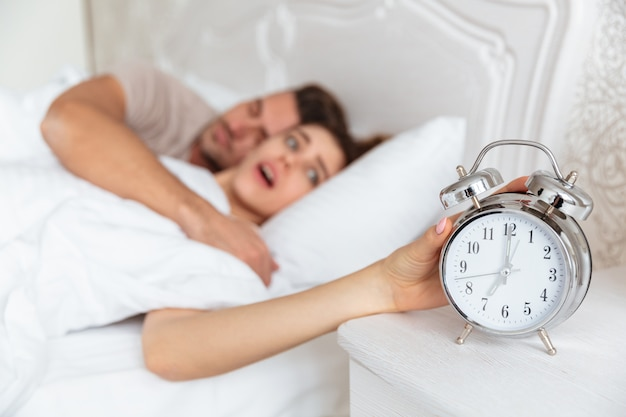 Side view of surprised couple sleeping together in bed