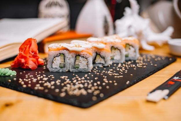 Вид сбоку суши филадельфия роллы в соусе с васаби и имбирем на подставке