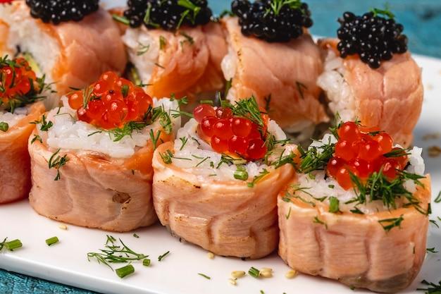 Вид сбоку суши ролл с запеченным лососем укропа красной и черной икрой на тарелке