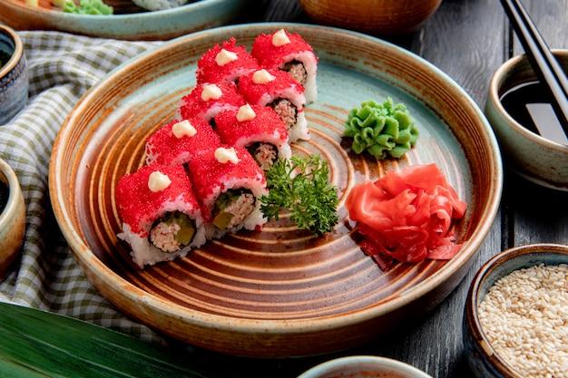 Vista laterale del rotolo di sushi con l'avocado del granchio coperto di caviale rosso con zenzero e wasabi su un piatto su legno