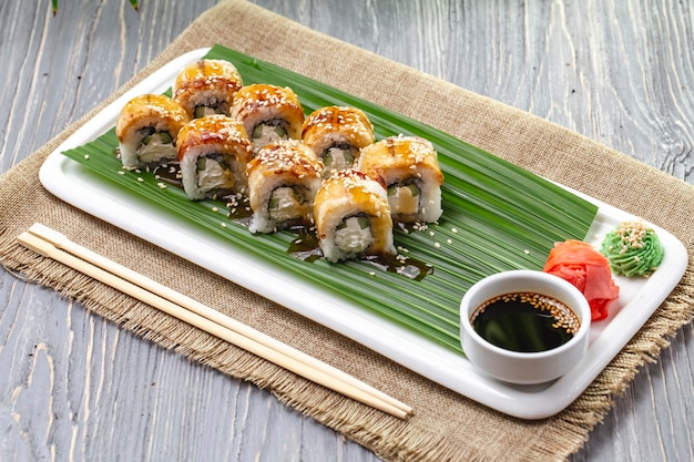 Side view sushi rolls with eel with ginger wasabi and soy sauce on a plate