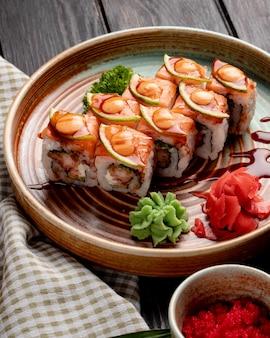La vista laterale dei rotoli di sushi con i gamberi l'avocado e la crema di formaggio è servito con lo zenzero e il wasabi su un piatto su legno