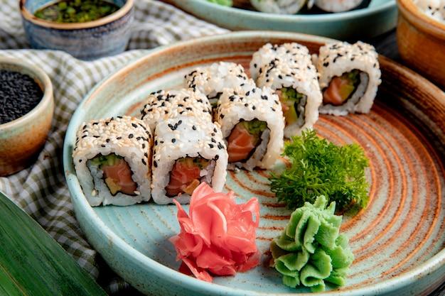 Vista laterale di involtini di sushi con tonno salmone e avocado ricoperti di sesamo su un piatto con wasabi e zenzero