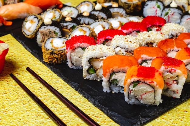 Вид сбоку набор для суши с курицей горячий ролл курица аляска ролл калифорния с крабовым мясом и икра тобико филадельфия с крабовым мясом и сливочным сыром на подносе