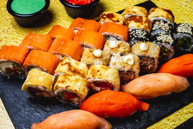 Side view sushi set egg roll with cucumber and salmon philadelphia with cream cheese maki salmon nigiri wasabi and ginger on the table