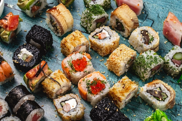 側面図寿司セットフィラデルフィアロールサーモンとアナゴワイルドライス寿司ロールディルカロフォルニアロールとテーブルのアラスカロール