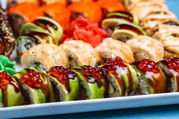 Вид сбоку суши-ролл с тигровыми драконами и креветками, соусом терияки с авокадо и имбирем на тарелке