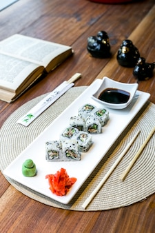 Side view sushi skin maki rolls with soy sauce ginger and wasabi on a plate and a book on the table